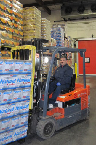 Employee moving cases of beer with fork lift.
